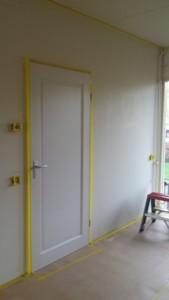 Werkvoorbereiding; afplakken van vloeren, kozijnen plinten en plafond.